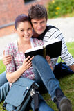Smiling couple of students reading a book. Sitting on the grass Royalty Free Stock Image
