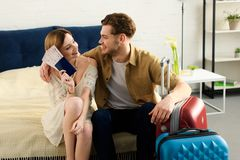 Smiling couple with suitcases on bed and holding tickets. With passports stock image