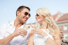 Smiling couple in sunglasses drinking wine in cafe Stock Photography