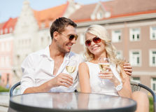 Smiling couple in sunglasses drinking wine in cafe Stock Photo