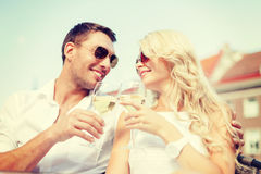 Smiling couple in sunglasses drinking wine in cafe Stock Image