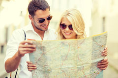 Smiling couple in sunglasses with map in the city royalty free stock image