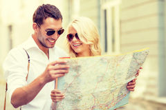 Smiling couple in sunglasses with map in the city Royalty Free Stock Photo