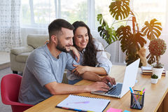Smiling couple surfing in laptop sitting at table stock photos