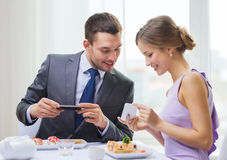 Smiling couple with sushi and smartphones Stock Photos