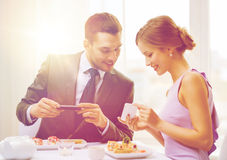 Smiling couple with sushi and smartphones Stock Image
