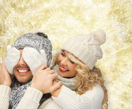 Smiling couple in sweaters and santa helper hats Royalty Free Stock Images