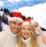 Smiling couple in sweaters and santa helper hats Royalty Free Stock Image