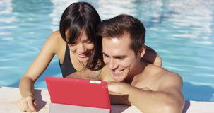 Smiling couple in swimming pool use digital device stock video
