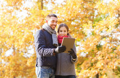 Smiling couple with tablet pc in autumn park Royalty Free Stock Photo