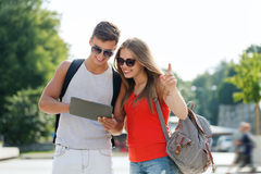 Smiling couple with tablet pc and backpack in city Stock Photography