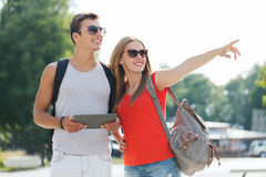 Smiling couple with tablet pc and backpack in city Stock Photo