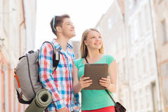 Smiling couple with tablet pc and backpack in city. Travel, vacation, technology and friendship concept - smiling couple with tablet pc and backpack in city stock images
