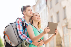 Smiling couple with tablet pc and backpack in city Royalty Free Stock Photos