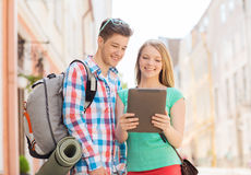 Smiling couple with tablet pc and backpack in city Royalty Free Stock Image