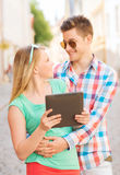 Smiling couple with tablet pc in city Royalty Free Stock Photos
