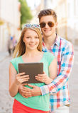 Smiling couple with tablet pc in city Royalty Free Stock Images