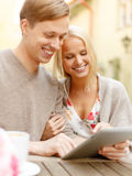 Smiling couple with tablet pc computer in cafe Royalty Free Stock Photos