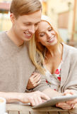 Smiling couple with tablet pc computer in cafe Royalty Free Stock Image
