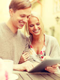 Smiling couple with tablet pc computer in cafe Stock Photos