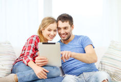 Smiling couple with tablet pc computer at home. Home, technology and relationships concept - smiling couple with tablet pc computer at home royalty free stock images