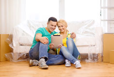 Smiling couple with tablet pc in new home Royalty Free Stock Image