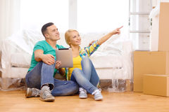 Smiling couple with tablet pc in new home Stock Images