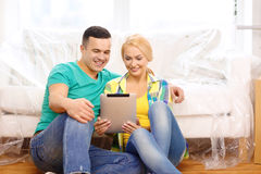 Smiling couple with tablet pc in new home Royalty Free Stock Photos