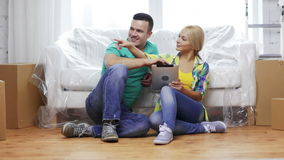 Smiling couple with tablet pc in new home Royalty Free Stock Photo