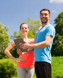 Smiling couple with tablet pc outdoors Stock Photos