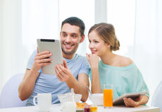 Smiling couple with tablet pc reading news Stock Photos