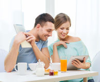 Smiling couple with tablet pc reading news Royalty Free Stock Photo