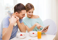 Smiling couple with tablet pc reading news Royalty Free Stock Photos