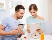 Smiling couple with tablet pc reading news Royalty Free Stock Photography