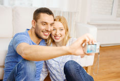 Smiling couple taking picture with digital camera Stock Photography