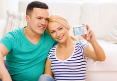 Smiling couple taking picture with digital camera Royalty Free Stock Photos