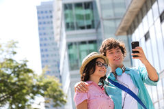 Smiling couple taking self portrait outside office building Stock Photos