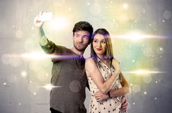 Smiling couple taking selfie in glitter light Royalty Free Stock Images