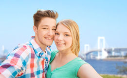 Smiling couple taking selfie over bridge Stock Image