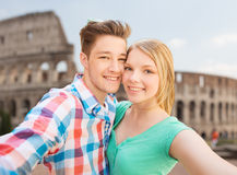 Smiling couple taking selfie over coliseum Royalty Free Stock Photography