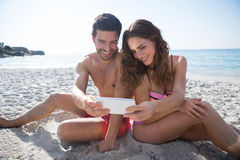 Smiling couple taking selfie while sitting at beach Stock Images