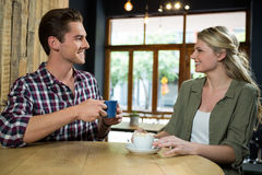 Smiling couple talking while having coffee at table in cafeteria. Smiling young couple talking while having coffee at table in cafeteria Royalty Free Stock Photography