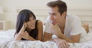 Smiling couple talking while laying down on bed Royalty Free Stock Image