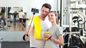 Smiling couple talking a selfie at gym. stock video
