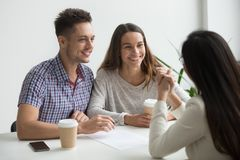 Smiling couple talking to real estate agent. Smiling millennial happy couple talking to broker in sales office, discussing buying first house, making successful royalty free stock images