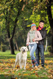 A smiling couple and their dog posing in the park. In autumn Stock Image