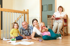 Smiling couple with their offspring and grandmother on floor at. Happy couple with their offspring and grandmother on floor at home Stock Images