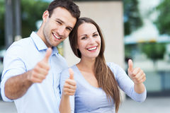 Smiling couple with thumbs up. Happy young couple with thumbs up Stock Image