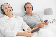 Smiling couple to music on their smartphones Royalty Free Stock Photos