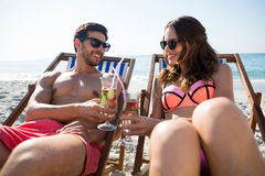 Smiling couple toasting drinks while relaxing on deck chairs at beach Stock Image